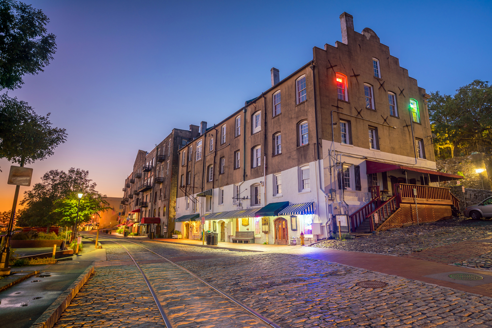 A street at night lit by lamps. River Street is a great place for shopping in Savannah