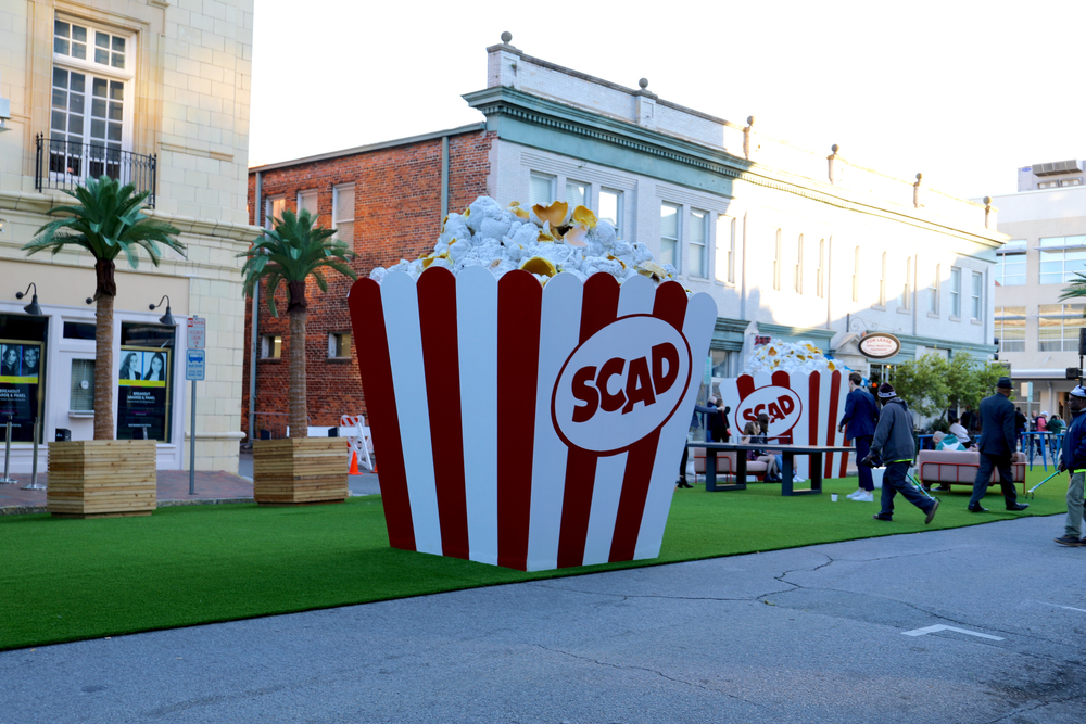a giant popcorn container with buildings in the background at Savannah College of Art and Design. The scad shop is a great place for shopping in Savannah