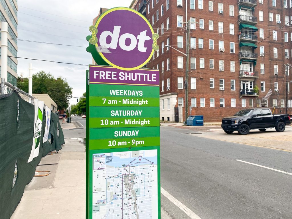 """The free shuttle stop on a street in Savannah. It is a tall green sign that says """"Free Shuttle"""" in white in a purple block. It then says the daily hours and a map of the route. On top of the green sign is a large circular attachment that is purple and says 'dot'. The street is a fairly normal street with a chain link fence by the sidewalk and a large brick apartment building across the street."""