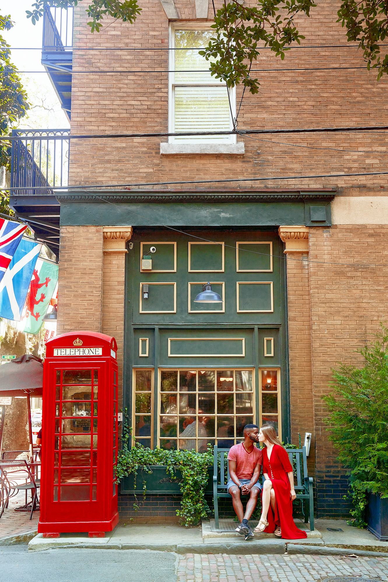 A couple sitting outside of a traditional British pub on a green bench. The Pub is mostly brick with green and yellow windows and trim. There is a classic British Telephone Booth next to a window looking into the pub. The couple is sitting on a green bench in front of the window and there is a window box with vines in front of the window. The woman in the couple is wearing a long red dress. The man in the couple is wearing a red heather shirt and denim blue shorts. They are kissing.