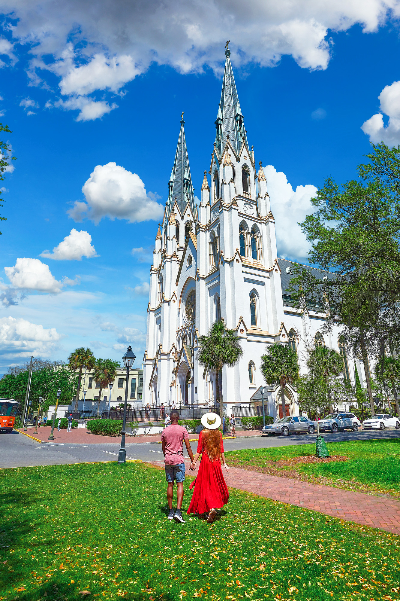 A man and woman holding hands in the grass looking at a large cathedral. The woman is standing in a bright red dress with her long hair down and wearing a cream colored sun hat looking up at the Cathedral Basilica of St. John The Baptist. The man is wearing a read heather shirt and denim blue shorts and is also looking up at the Cathedral. The Cathedral is very large and cream with an intricate Gothic Revival architectural design. The trimmings of the church are gold.
