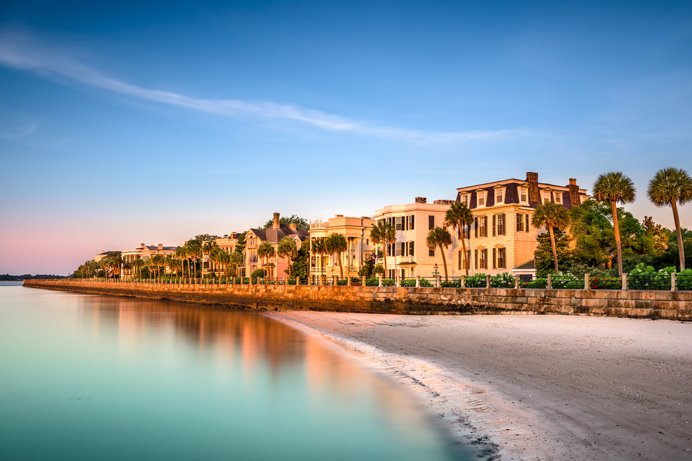 The Battery from the beach, a historic street of homes. Most of the homes are cream or terracotta in color. It is sunset and the water from the beach is calm.