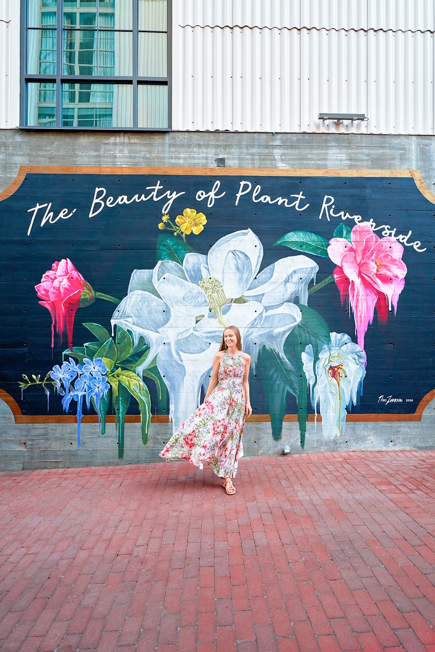 A woman in a white floral sun dress standing in front of a large mural. The mural is black and shaped like a classic movie ticket. The painting says 'The Beauty of Plant Riverside' and has white, pink, and blue flowers painted on it. In some parts, the flowers are intentionally dripping, like the paint is wet.