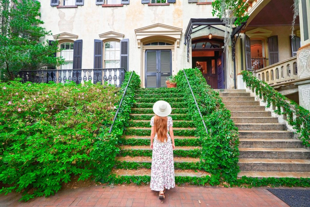A woman in a white floral maxi dress with long hair and a sun hat standing on the sidewalk in front of a set of stairs covered in ivy. The stairs lead to a private historic home in Savannah. Next to the stairs is an overgrown garden on one side, and a set of concrete stairs on the other side. Its one of the coolest Savannah photo spots