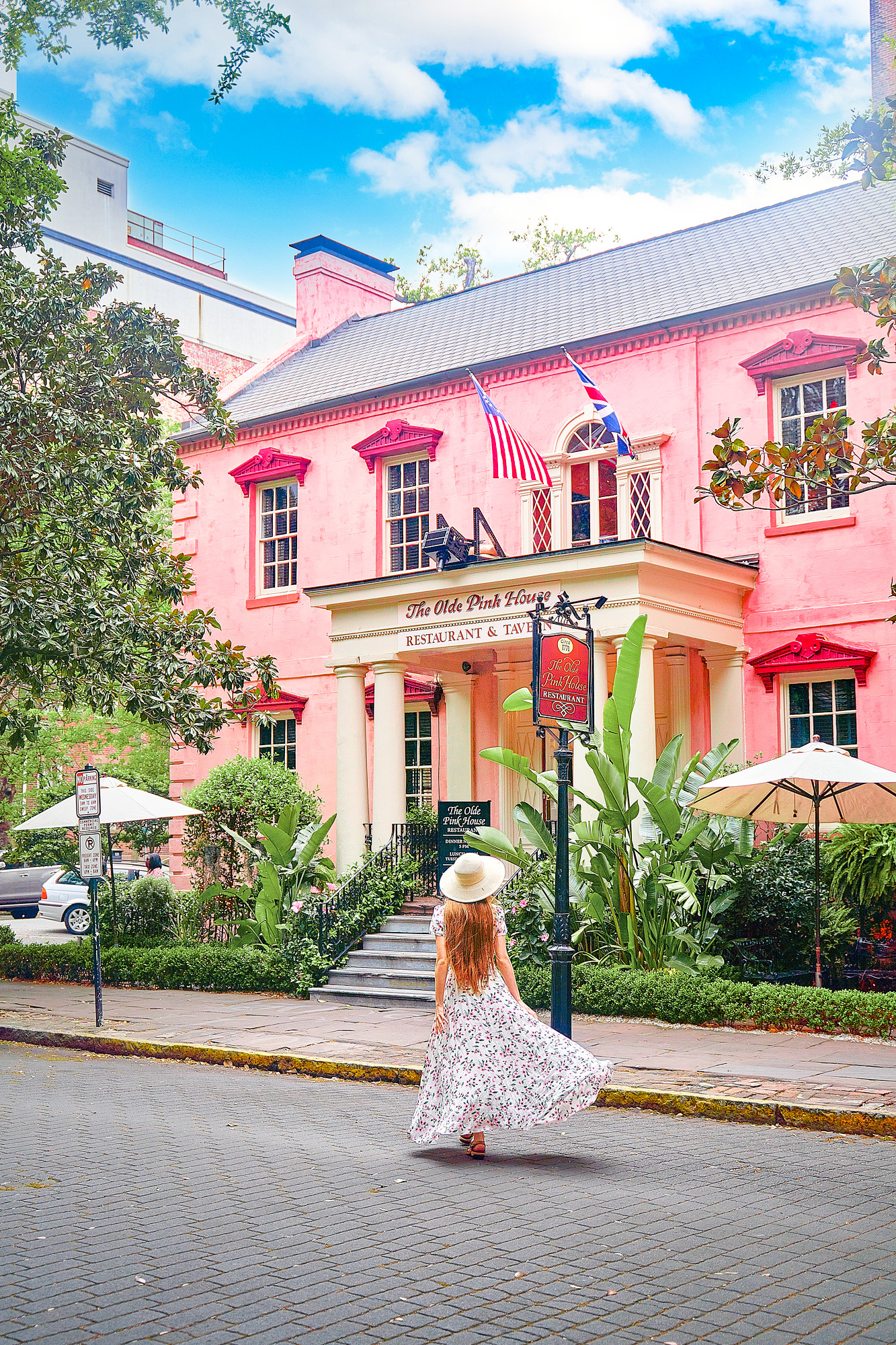 A woman standing on a cobblestone street in a long floral dress with her long hair down and a white sun hat. She is standing in front of The Olde Pink House, a historic building that is now a restaurant and tavern. It is a large building that is kind of the color of pepto bismol. The windows have a darker pink trim. There are umbrellas and lots of greenery in front of the building. A beautiful Savannah photo spots.