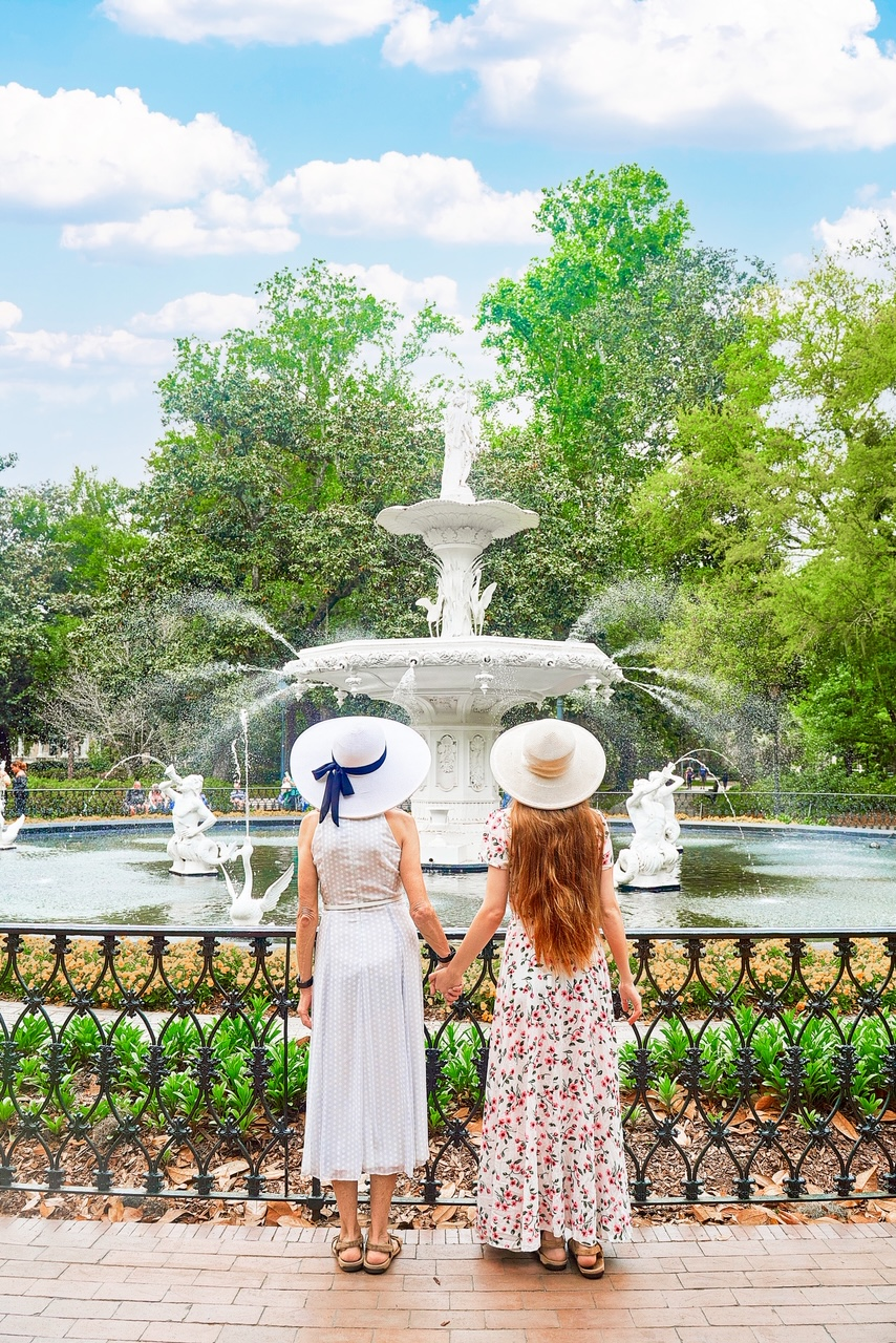 Two women standing in front of the famous Forsyth Fountain holding hands. One woman is wearing a white polka dot sun dress and a white sun hat with a blue bow. The other has long hair, and is wearing a white floral maxi dress with a tan sunhat. It is a sunny day and the fountain is spraying water from all sides.