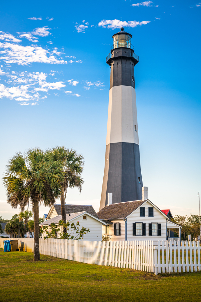 A black and white striped lighthouse on Tybee Island. Next to the lighthouse there are several small white buildings with black shutters. There is a white picket fence and palm trees on the property.