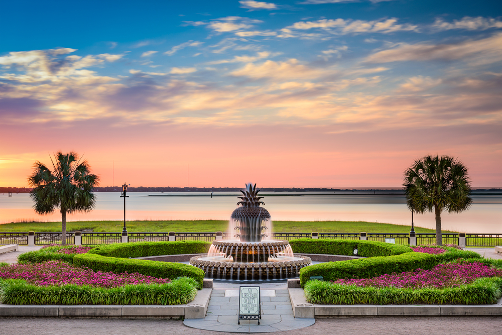 The famous Palmetto Water Fountain surrounded by manicured shrubs and plants looking out to Charleston Harbor. There are palm tress and it is sunset.