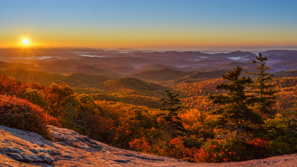 A picture of the sun setting over the Blue Ridge Parkway as seen from Beacon Heights Overlook in the fall.
