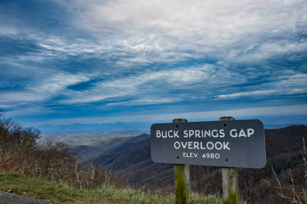 """A photo of a sign that says, """"Buck Springs Gap Overlook Elevation 4,980"""" with the forest of brown and orange trees covering the mountains in the background."""