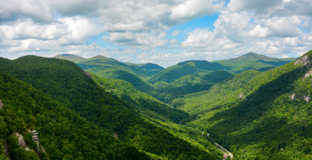 A picture of green forested mountains of the Blue Ridge Parkway on a cloudy day seen from Chimney Rock Mountain Overlook.