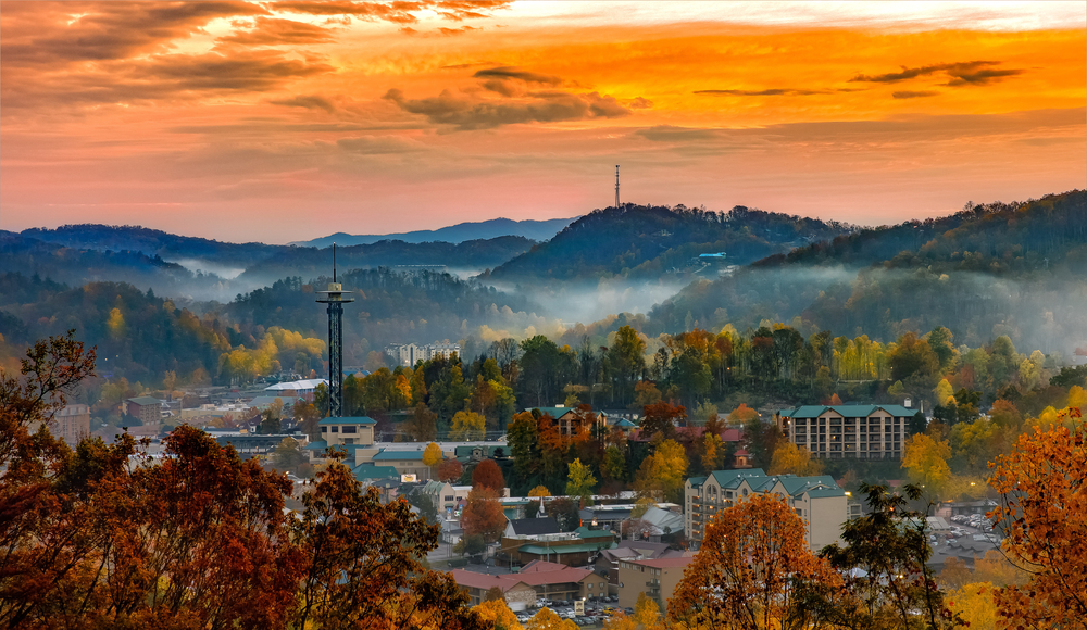 cute misty town of gatlinburg tennessee with fall foliage and sunrise in the background