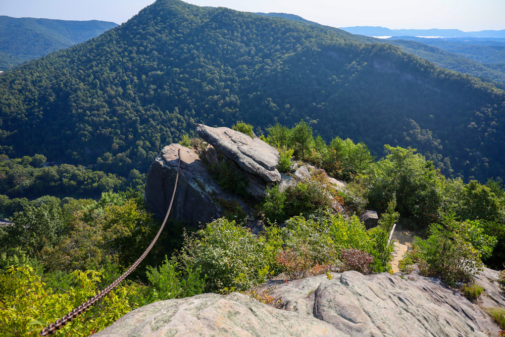 Photo of a large rock with a chain connected to it overlooking a tree-covered mountain landscape at Pine Mountain State Park.