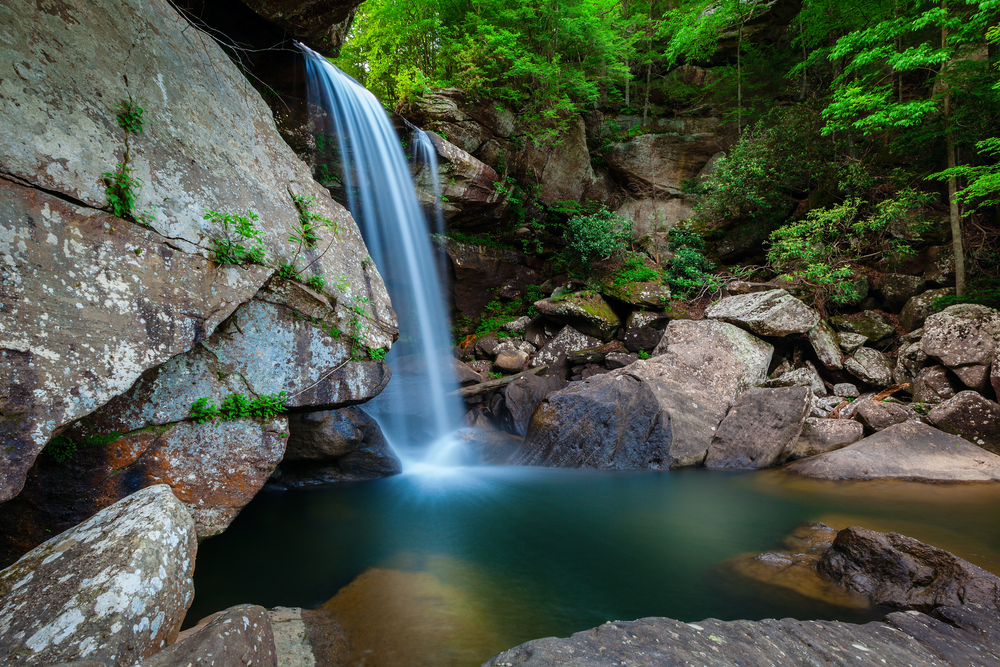 Photo of Eagle Falls flowing over a rocky cliff  into a blue natural pool below.