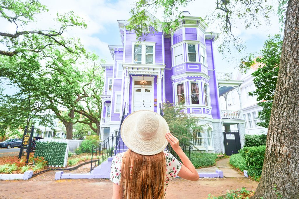 woman holding her hat in front of purple house in Savannah georiga