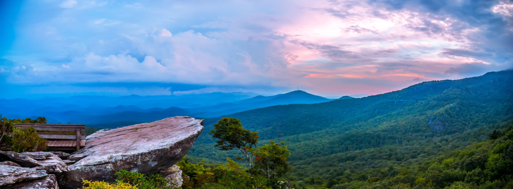 A photo off the Rough Ridge Overlook base overlooking the valley and mountain scenery of the Blue Ridge Parkway at sunset.
