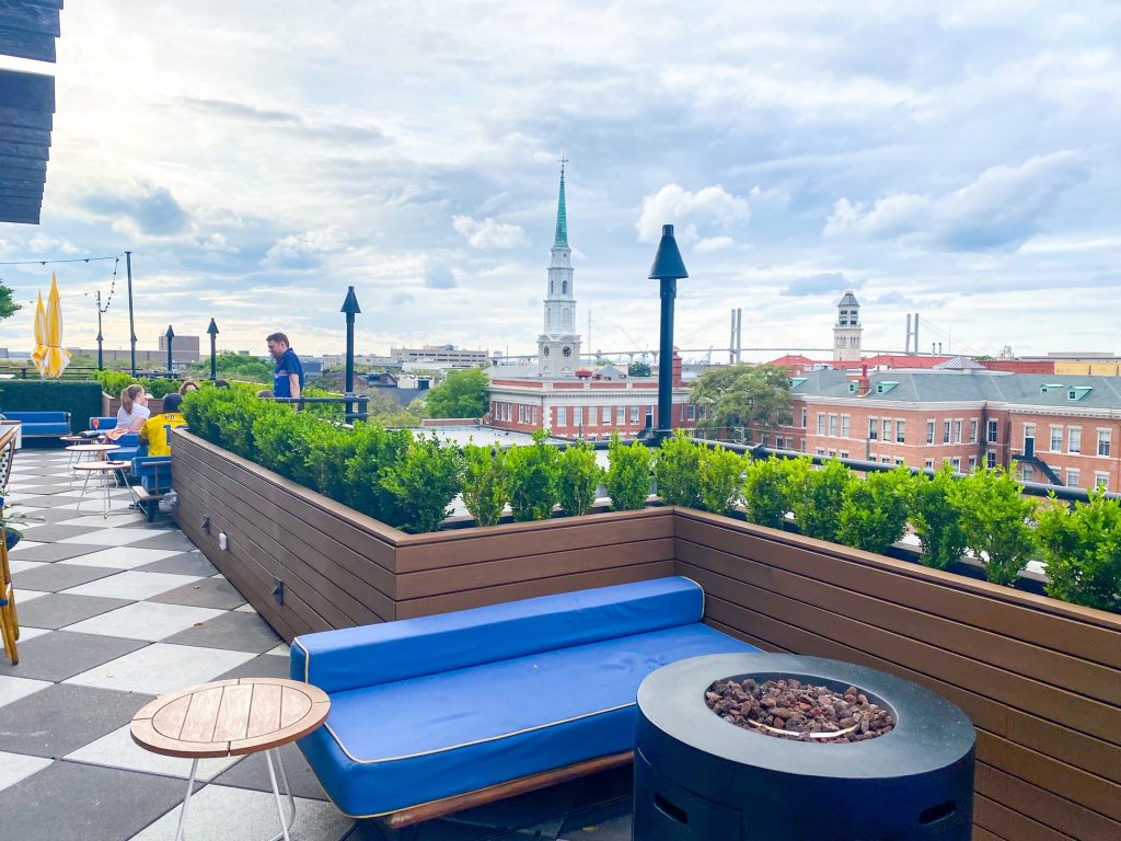 A rooftop bar that looks out onto the city of Savannah Georgia. There are seating areas with benches with blue cushions and yellow and white striped umbrellas. There are small circular wooden accent tables and a black firepit. Surrounding the area is a tall wooden planter with boxwood shrubs in it. The floor is black and white parque. It is one of the best Savannah photo spots.
