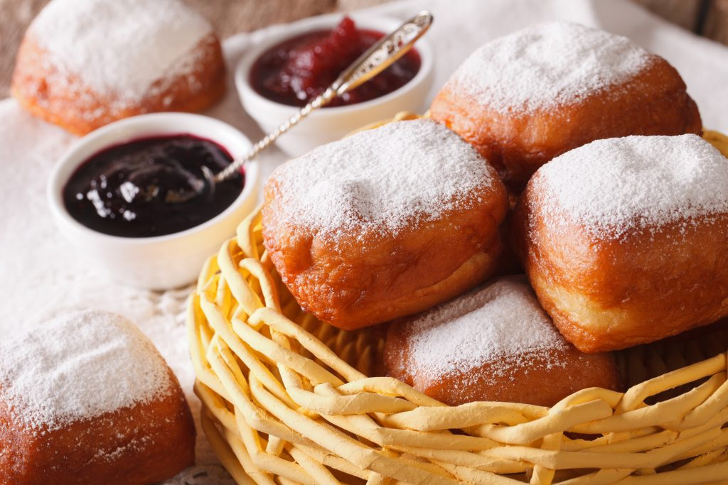 A basket of Beignets on a table with some jam