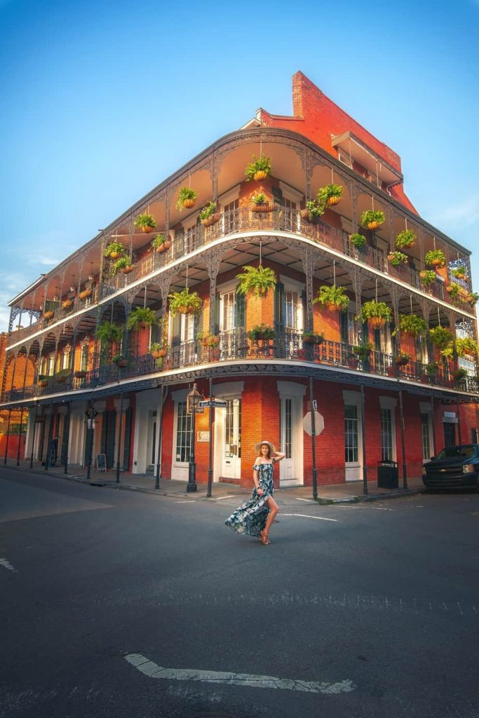 A girl stood on a street in the French Quarter with a building with balconies in the background