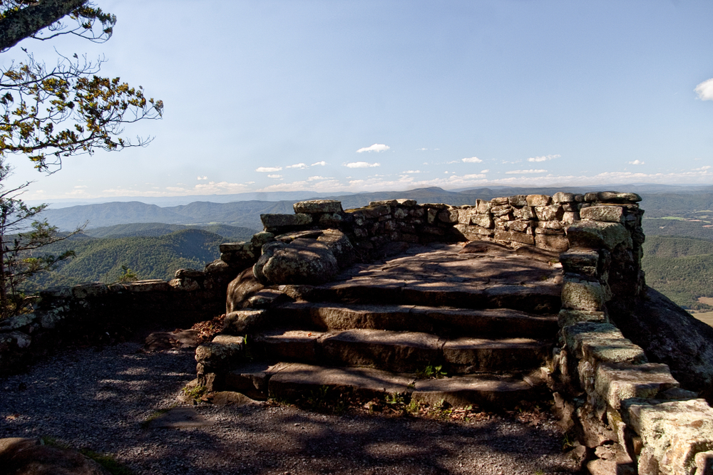 A picture of stone steps leading to the base of Thunder Ridge Overlook where you can see the mountains of the Parkway and clouds that are speckled in the blue sky.