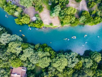 An aerial shot of the people tubing the crisp blue Guadalupe River that cuts through the center of a forest makes this one of the best weekend getaways from Dallas.