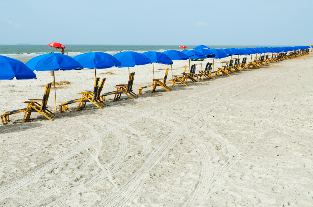 beach chairs lined up along the sand with blue umbrellas