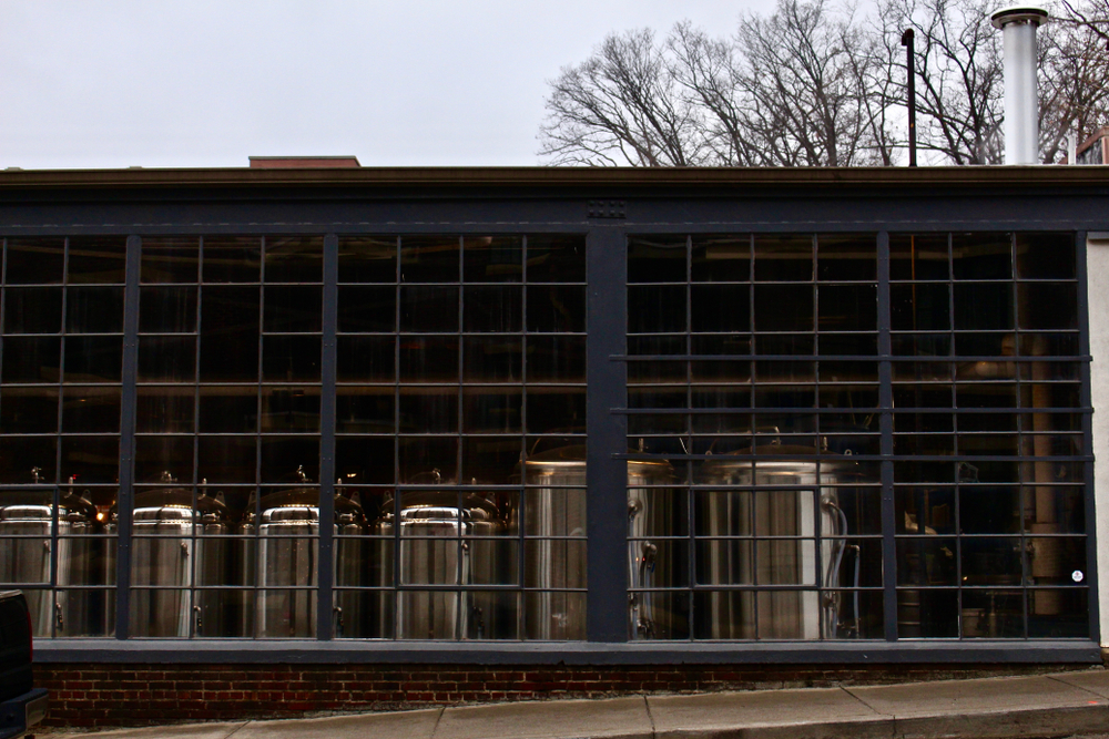A black building with lots of windows on the front. Through the windows you can see silver brewing tankards in the brewery.