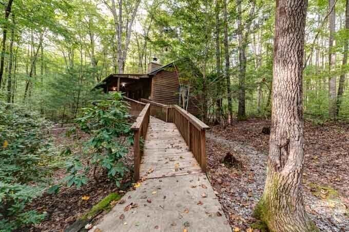 A cabin in the woods with a walkway.