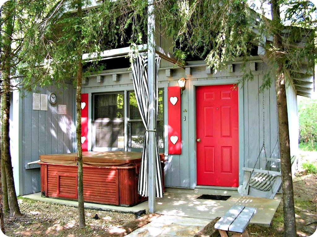 A grey cabin with a red door