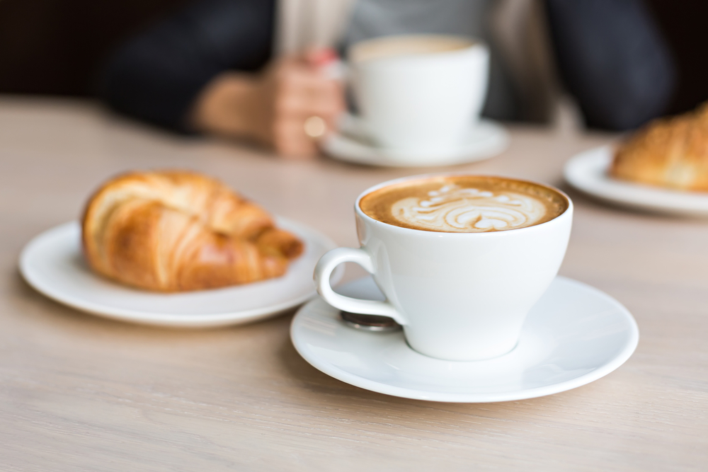 A latte in a white cup with a white plate that has a croissant on it.