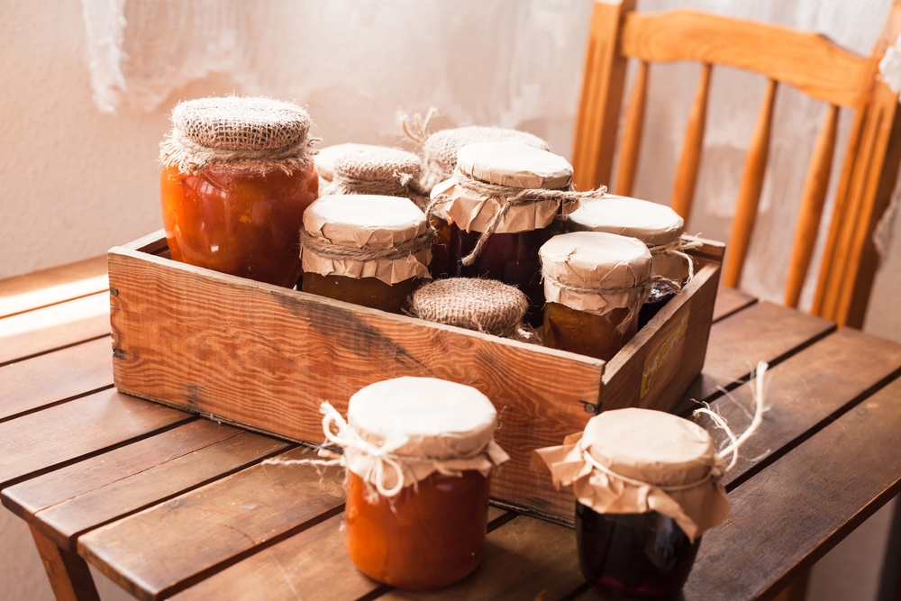 Jars of jam and jelly on a wooden table with a wooden chair behind it. The jars have burlap and twine on the top of them.