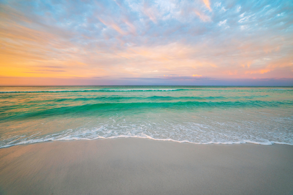 pristine beach in florida at sunset with blue water