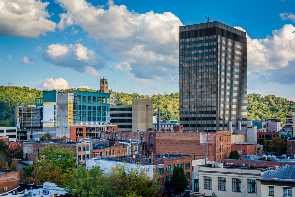 The view of Downtown Asheville on a sunny day. There are old buildings and a taller building covered in windows. Behind the buildings is a mountain covered in trees.