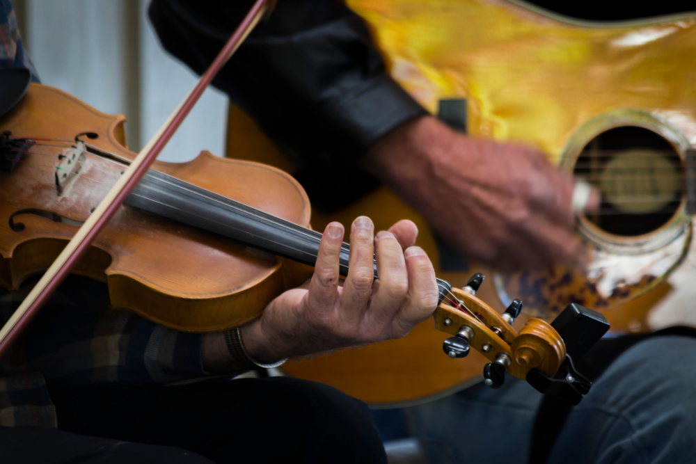 A person playing the fiddle. You can see someone playing the guitar behind them. You can only see the players hands, not their face or anything else.