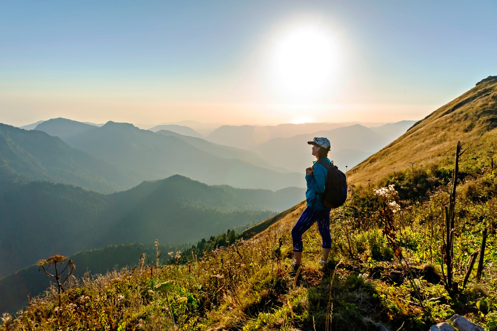 A woman standing on the side of a mountain looking out onto the blue ridge mountains. She is wearing a hat and a backpack. The sky is hazy but it is sunny.