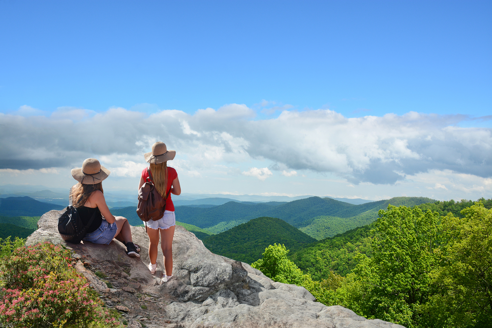 Two women wearing sun hats, one is standing and one is sitting on a rocky cliff edge. They are looking out onto the Blue Ridge Mountains in the distance. You can see green trees nearby. The clouds are hanging low but the sky is blue.