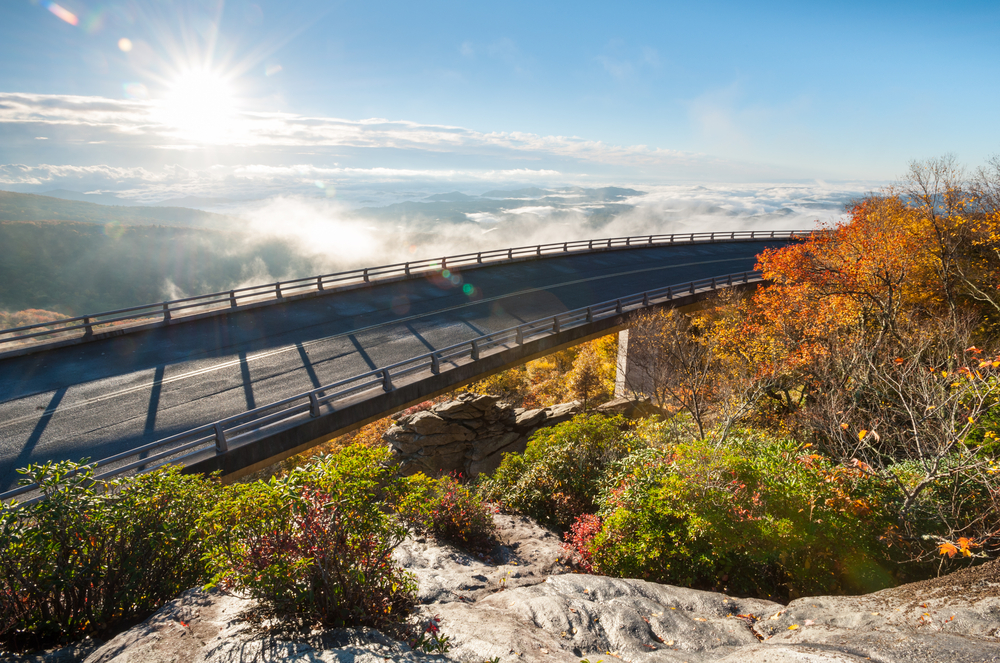 An overhead view of the Linn Cove Viaduct in the fall. There are clouds in the distance and it is very sunny.