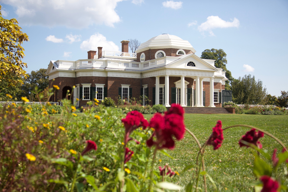 Thomas Jefferson's private home called Monticello. It is a Greek Revival style home with brick and white accents. It has a large green lawn with yellow and red flowers.