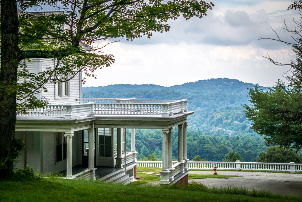 The side of the Moses Cone Manor, a white home with a large porch. Behind the home, you can see mountains covered in trees. The sky is cloudy.