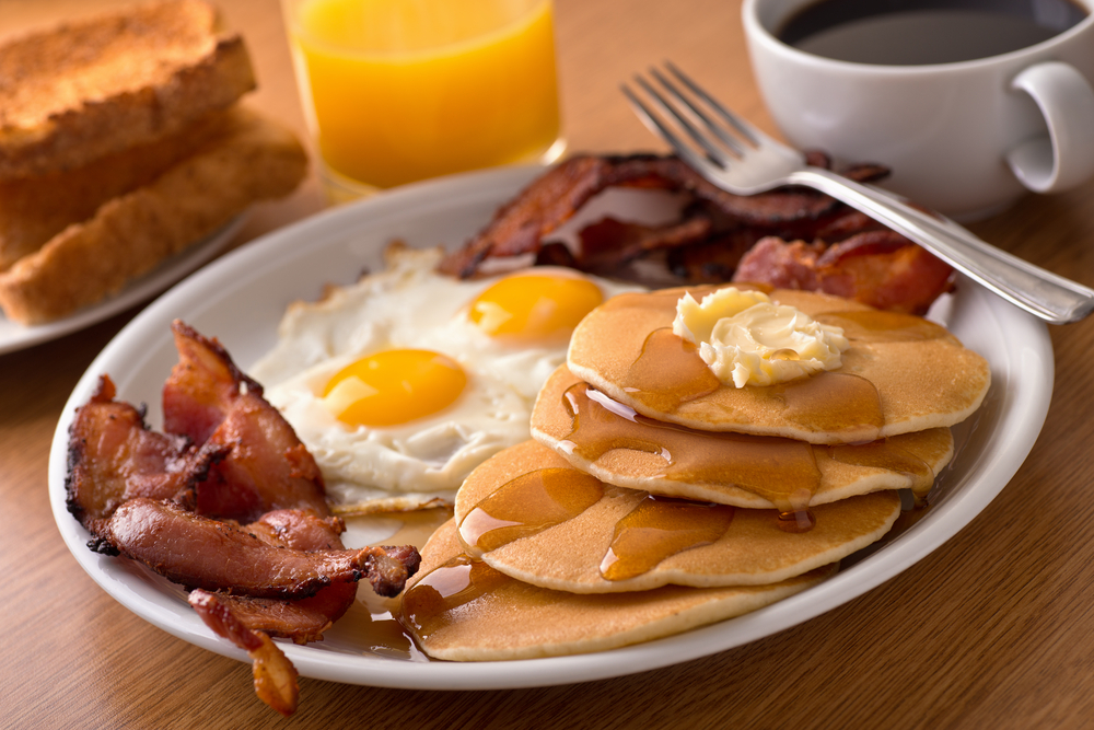 pancakes, bacon, and eggs on a plate. coffee and orange juice near by