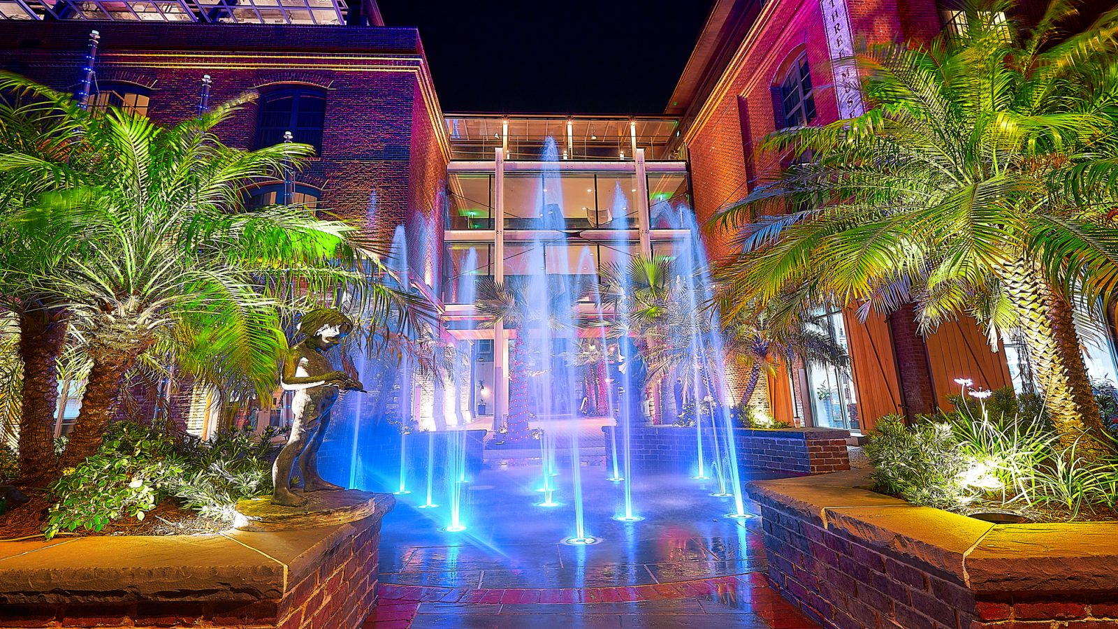 The splash pad of the Plant Riverside District at night, illuminated by lights.