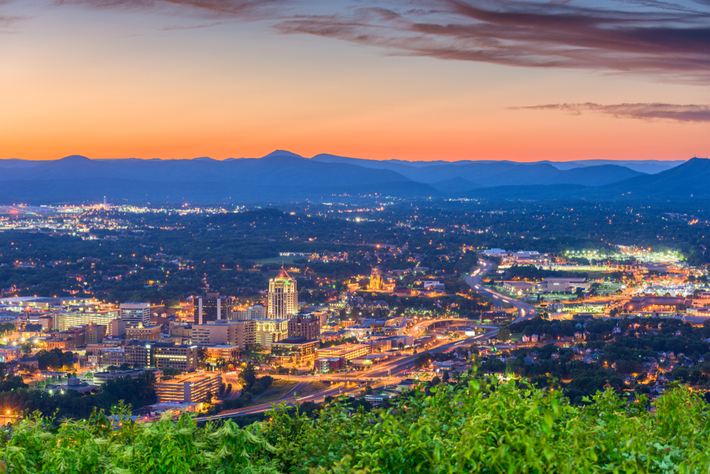 An aerial view of the city of Roanoke all lit up. It is twilight and you can see the mountains in the distance. The sky is a peach color against the blue silhouette of the mountains.