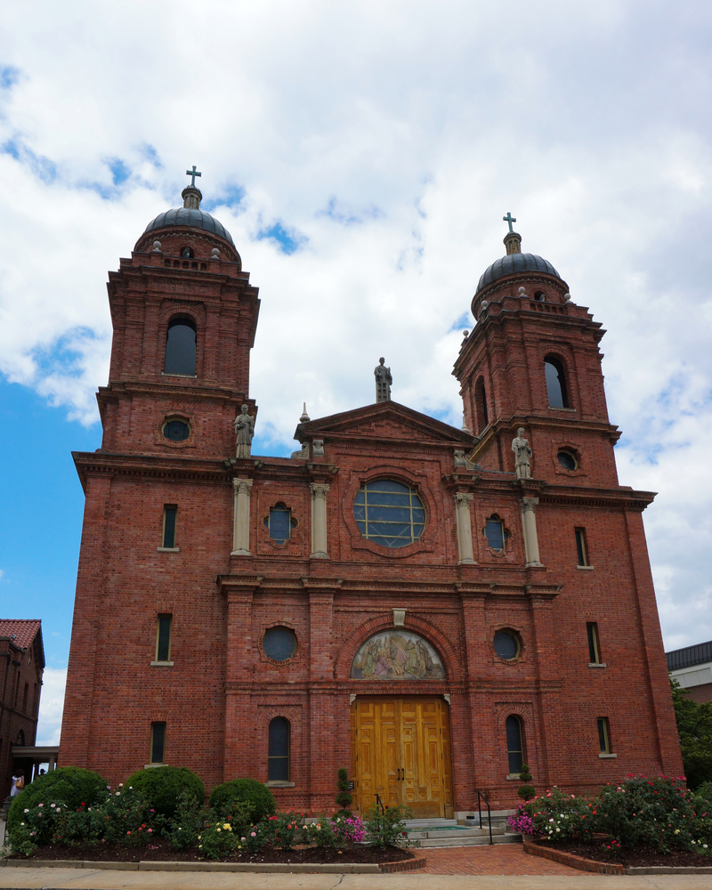 The Basilica of Saint Lawrence in Downtown in Asheville. It is a brick Spanish Gothic style building. It has circular and slit windows, carvings on the top of people, and large wooden doors. The front of the church has flower beds with yellow, red, and pink flowers in it.