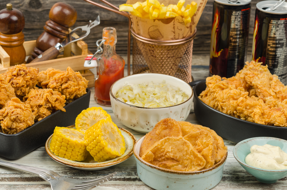 A selection of biscuits, fried chicken, corn, coleslaw, and fries. It is a on a whitewashed table.