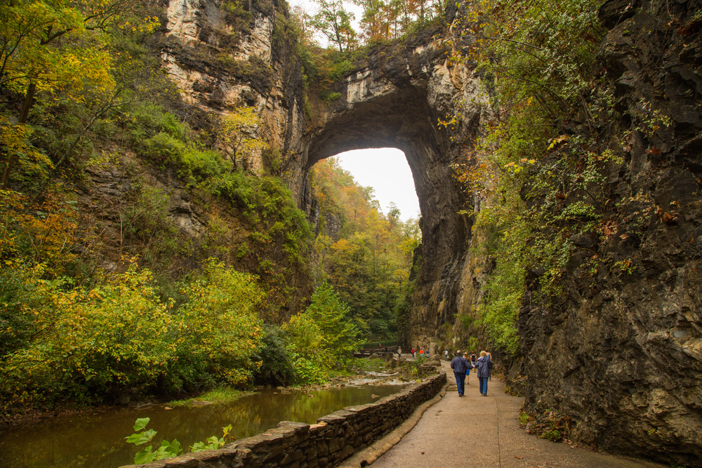 The Natural Bridge in Virginia. It is a large nature made rock arch in the woods. There are people walking on a trail underneath it. It's a great stop on a Blue Ridge Parkway drive.