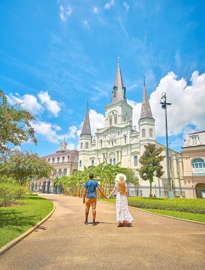 Two people holding hands in front of a church in the French quarter