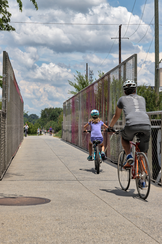 A father and daughter biking along the Beltline path in Atlanta,