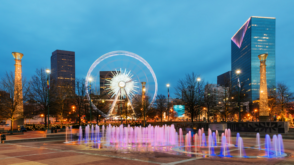 Centennial Olympic Park with the water fountains and Sky View Ferris Wheel with the backdrop of downtown Atlanta at nighttime.