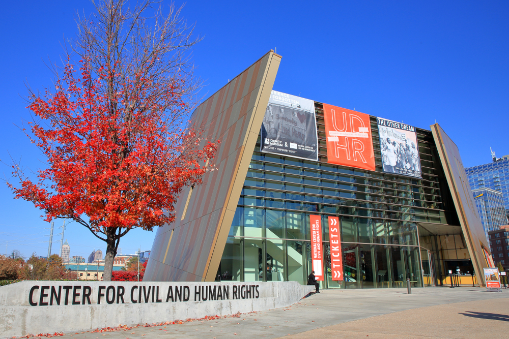THe outside of the building for the center for Civil and Human Rights with a beautiful red tree. A must visit for any weekend in Atlana