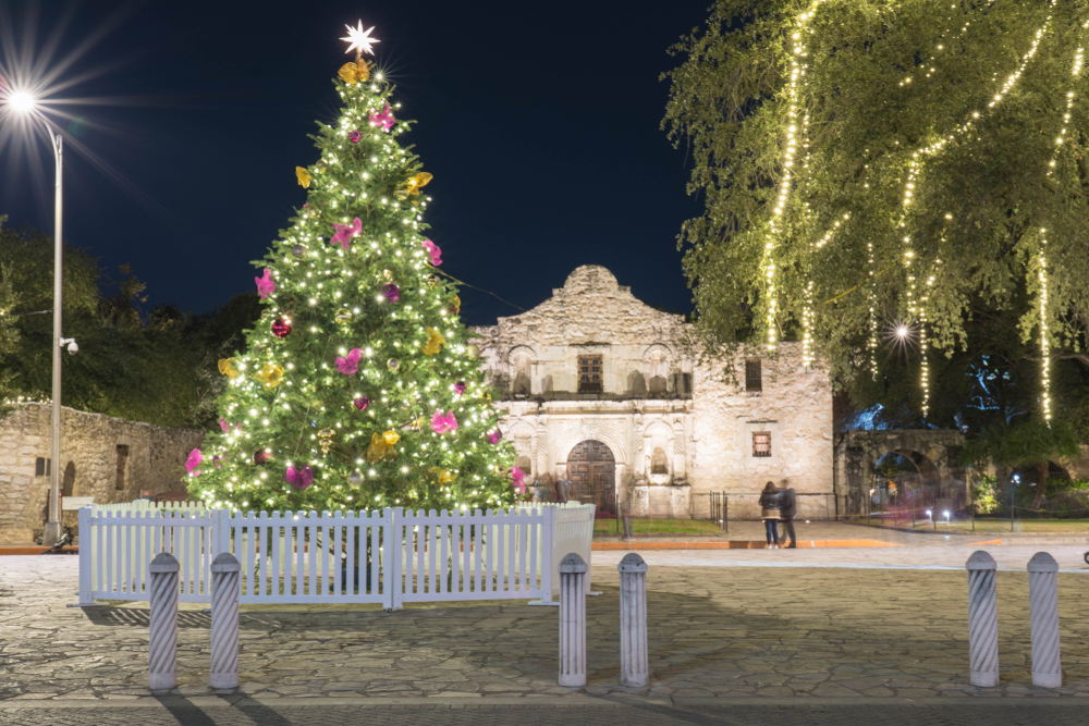 A picture of a large Christmas tree covered in lights and ornaments in front of the Alamo in San Antonio, Texas.